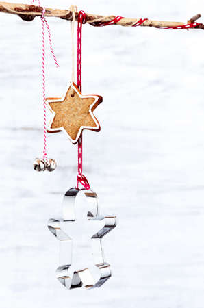 Christmas background with xmas decoration gingerbread man cookie cutter, star and bell hanging off a branch photo