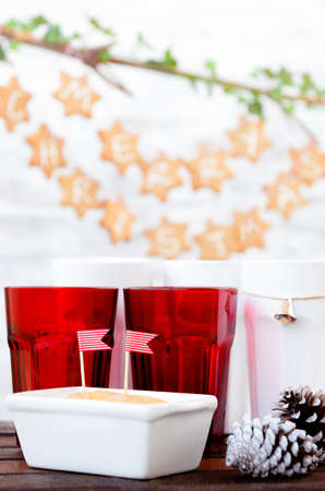 Christmas decoration table with red cups, cake with striped flags, pine cones and gingerbread stars hanging in the background photo