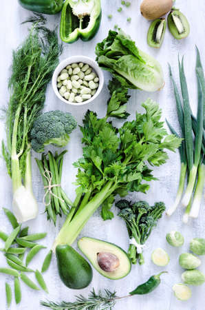 Collection of green vegetables on rustic white background from overhead, broccoli, celery, avocado, brussel sprouts, kiwi, pepper, peas, beans, lettuce,