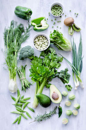 brussel: Variety of green vegetables produce on rustic white background from overhead, broccoli, celery, avocado, brussel sprouts, kiwi, pepper, peas, beans, lettuce