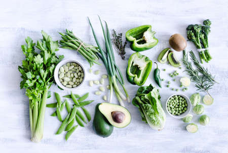 brussel: Collection of green produce from farmers market on rustic white background from overhead, broccoli, celery, avocado, brussel sprouts, kiwi, pepper, peas, beans, lettuce, Stock Photo