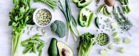 Zdravá šíření zeleniny na rustikální bílém pozadí z horní, brokolice, celer, avokádo, růžičková kapusta, kiwi, paprika, hrášek, fazole, hlávkový salát, photo