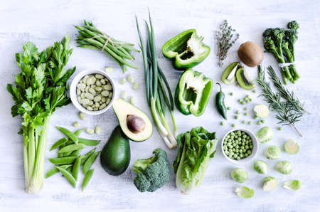 Fresh green vegetables variety on rustic white background from overhead, broccoli, celery, avocado, brussel sprouts, kiwi, pepper, peas, beans, lettuce, Stock Photo