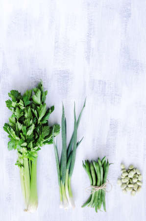 Vegetables from the farmers market on a white rustic backgroun, celery spring onion beans shot from overhead photo