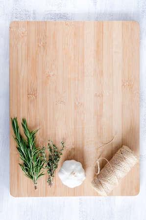 まな板: 新鮮なハーブ、ニンニク、麻ひも竹まな板背景を調理のオーバーヘッドからのロールバックします。