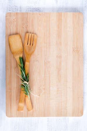 まな板: 木製の道具竹まな板オーバーヘッド、食品の背景からのローズマリーと結ばれる 写真素材
