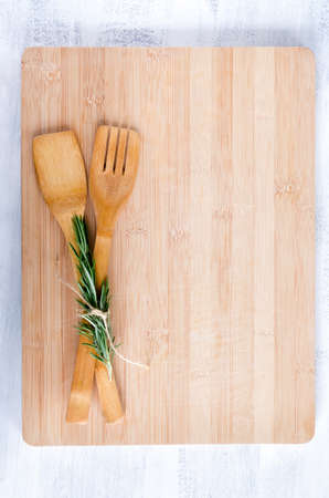 chopping board: wooden utensils tied with rosemary on bamboo chopping board from overhead, food background