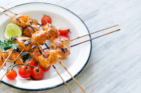 Grilled chicken skewers served with tomatoes lime and coriander on a rustic enamel plate photo