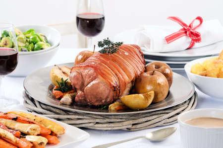beine spreizen: Weihnachtsessen mit Schweinebraten, Kartoffeln, Honig glasierte Karotten, Rosenkohl Seiten und Wein auf einem festlich gedeckten Tisch