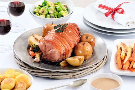 Christmas table laid with pork roast, potatoes, vegetables brussel sprouts sides and wine  photo