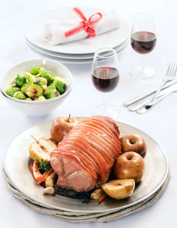 Thanksgiving table setting with pork roast, baked apples, vegetable sides and wine  photo