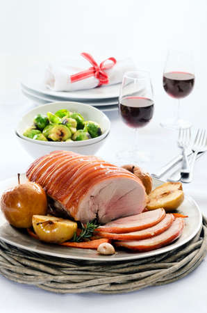 Sliced pork roast served at a table set with vegetable sides, wine and cutlery photo