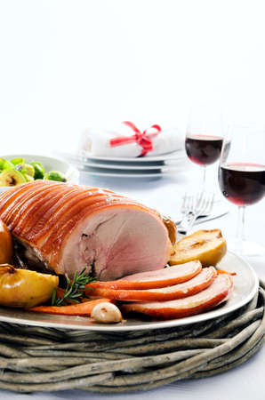 the sides: Sliced pork roast served at a table set with vegetable sides, wine and cutlery, plenty of copy space Stock Photo
