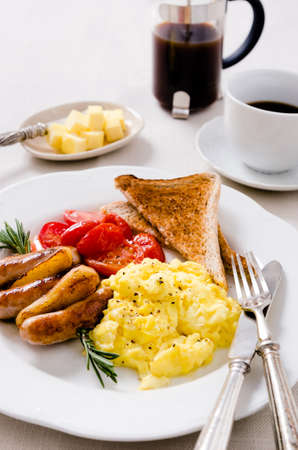 Scrambled eggs with fried tomatoes, pork sausages chipolata and wholemeal toast, full breakfast served with coffee photo