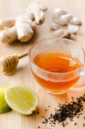 Cup of tea with ginger, lemon, honey, garlic for soothing detox drink photo