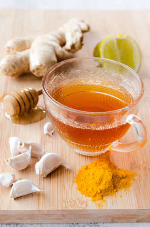 Cup of tea with ginger, lemon, honey, garlic, tumeric for spicy detox drink photo