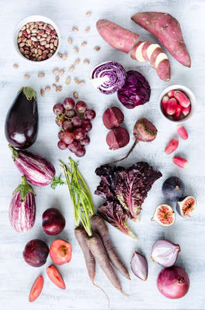 Collection of fresh purple toned vegetables and fruits on white rustic background, eggplant, beetroot, carrot, fig, plum, aubergine, cabbage, grapes, radishes, loose leaf lettuce photo