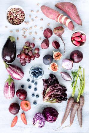 loose leaf: Colecci�n de verduras frescas p�rpuras entonadas y frutas sobre fondo blanco r�stico, berenjena, remolacha, zanahoria, higo, ciruela, berenjena, col, uva, los r�banos, la lechuga de hojas sueltas Foto de archivo
