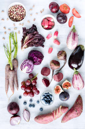 fresh produce: Collection of fresh purple toned vegetables and fruits on white rustic background, eggplant, beetroot, carrot, fig, plum, aubergine, cabbage, grapes, radishes, loose leaf lettuce