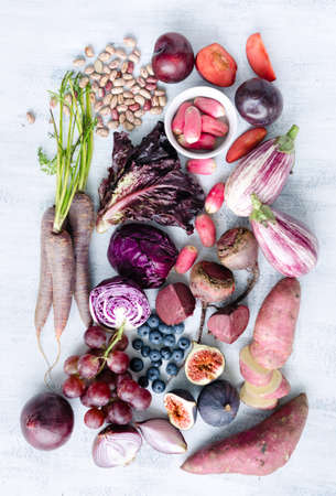 fruit harvest: Collection of fresh purple toned vegetables and fruits on white rustic background, eggplant, beetroot, carrot, fig, plum, aubergine, cabbage, grapes, radishes, loose leaf lettuce