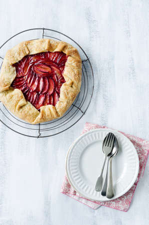 Whole plum galette, a french dessert pie tart with sweet homemade crust overhead with serving cutlery photo
