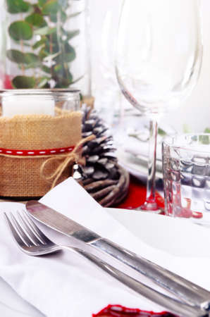Christmas table place setting with wine glasses in red and white with pine cones, candles and leaf centerpiece Stock Photo - 22967134