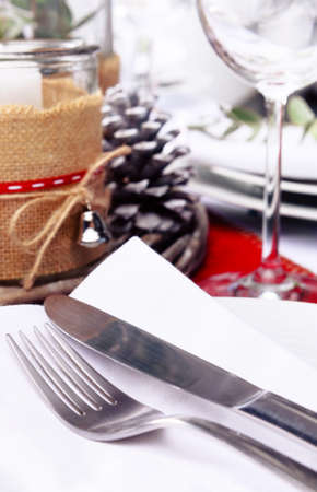Close up of cutlery at christmas table place setting in red and white with pine cones, candles and leaf centerpiece Stock Photo - 22967135