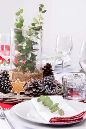 Christmas table place setting in red and white and rustic pine cone centerpiece Stock Photo - 22967136