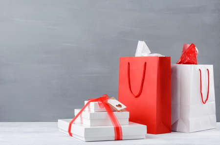 Shopping bags and gift boxes or presents on table top, on grey background with plenty of copy space christmas xmas seasonal holiday photo