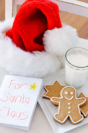 holiday tradition: Handwritten note to santa claus with milk and cookies, christmas holiday tradition Stock Photo