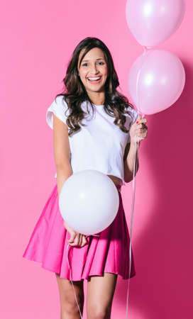 Pretty girl holding pink and white balloons on pink background, playful cute party celebration photo