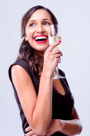 Pretty woman holding a glass of champagne looking away, wearing a little black dress for new years eve party celebration photo
