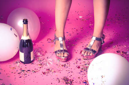 Pair of feet at a new years eve countdown party with confetti, champagne and balloons on the floor photo
