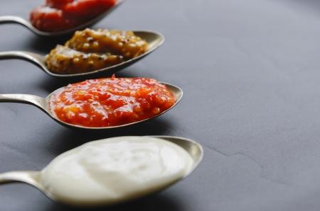 wholegrain mustard: Variety of condiments on vintage spoons on slate background, mayonnaise, tomato sauce, mustard and sweet chilli jam