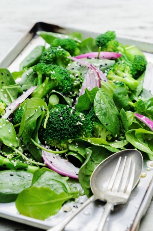 roasted sesame: Tray of fresh tossed green salad leaves with broccoli, spinach topped with roasted sesame seeds and red onion