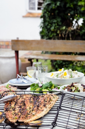 Table full of side dishes, variety assortment of salads with a whole grilled fish for a party gathering in the garden entertaining outdoors photo