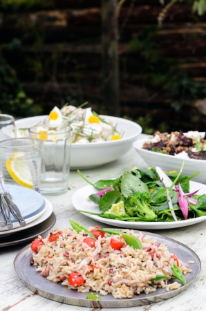 Garden summer entertaining, buffet style with different salads on the table, green leafy, brown rice pilaf with cherry tomatoes photo