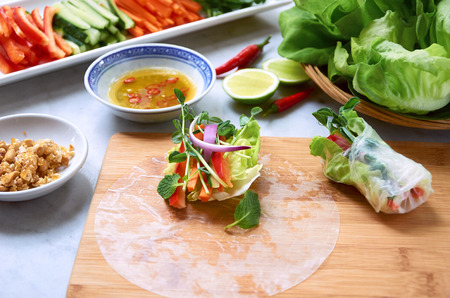 Wrapping fresh Vietnamese spring rolls with vegetables and herbs, healthy lunch asian meal with dipping sauce photo
