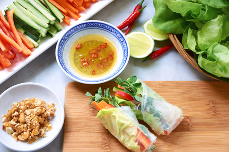 Fresh Vietnamese spring rolls filled with vegetables and herbs, healthy lunch asian meal with dipping sauce photo
