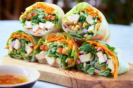 Vietnamese rice paper spring rolls with fresh vegetables and chicken strips, healthy asian wraps photo