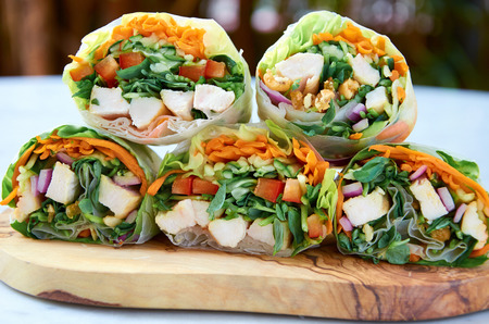 Cross section of healthy vegetable wraps with carrots, greens and chicken photo