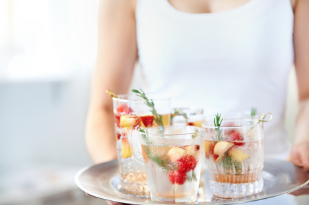 Cropped image of a woman holding a tray of cocktails, mocktails, refreshing drinks with garnish, raspberries and sliced apple in them photo