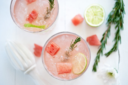 Watermelon fruity cocktail mocktail drink decorated with\ cubes of fresh watermelon and rosemary