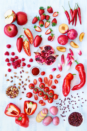 fresh produce: Collection of fresh red toned vegetables and fruits raw produce on white rustic background, peppers capsicum chilli strawberry raspberry pomegranate tomato paprika azuki beans plum Stock Photo