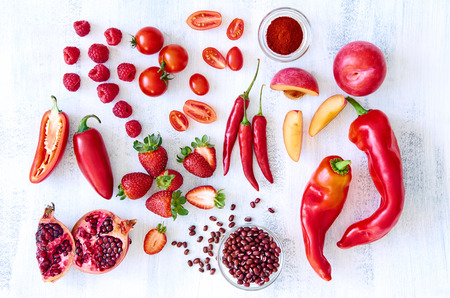 Collection of fresh red toned vegetables and fruits raw produce on white rustic background, peppers capsicum chilli strawberry raspberry pomegranate tomato paprika azuki beans plum photo