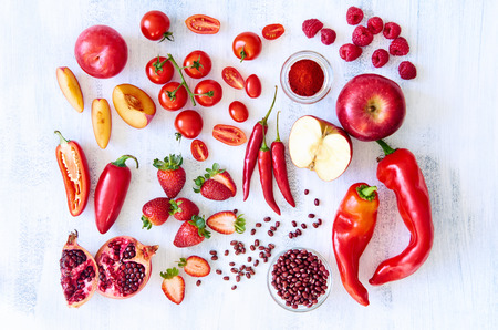 Collection of fresh red toned vegetables and fruits raw produce on white rustic background photo