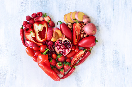 heart: Collection of fresh red vegetables and fruits arranged in a heart shape on white rustic background strawberry raspberry pomegranate peppers capsicum chilli potato beans legumes Stock Photo