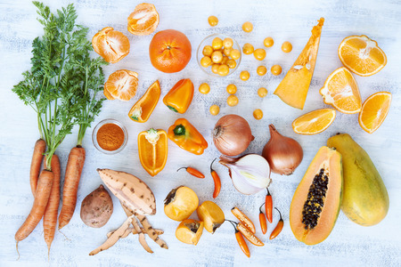 Selection of assorted fresh orange toned vegetables and fruit raw produce on white rustic background, pumpkin butternut carrot papaya pawpaw capsicum pepper sweet potato cherry tomatoes chilli orange photo
