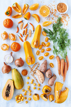 Collection of fresh orange toned vegetables and fruit raw produce on white rustic background, pumpkin butternut carrot papaya pawpaw capsicum pepper sweet potato cherry tomatoes chilli orange photo