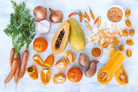 naranja color: Horizontal de arriba de color naranja en tonos verduras y frutas frescas productos crudos sobre fondo blanco r�stico, tomates calabaza butternut zanahoria papaya pimienta pimiento camote naranja cereza chile